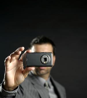 Uomo d'affari che prende le foto, macchina fotografica mobile