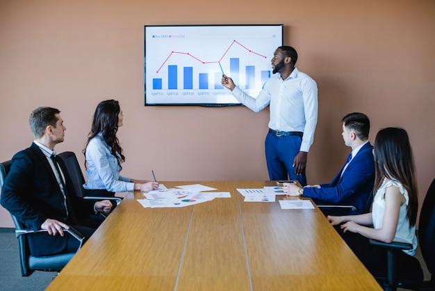 Uomo d'affari che presenta grafico in riunione