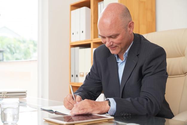 Uomo d'affari che progetta la sua giornata di lavoro