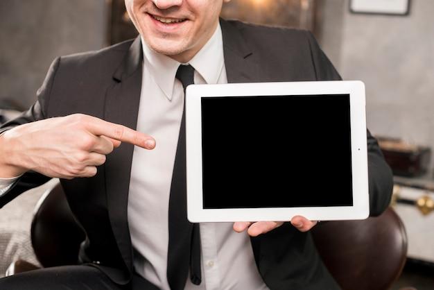 Uomo d'affari che punta al tablet con schermo vuoto
