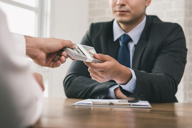 Uomo d'affari che riceve soldi dopo la firma del contratto
