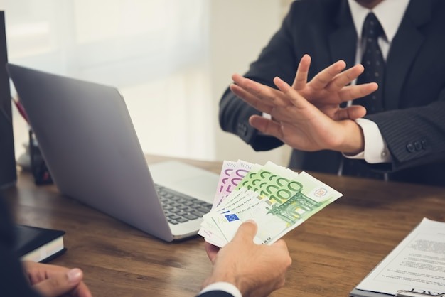 Uomo d'affari che rifiuta denaro, banconote in euro, dal suo partner mentre stipula un contratto