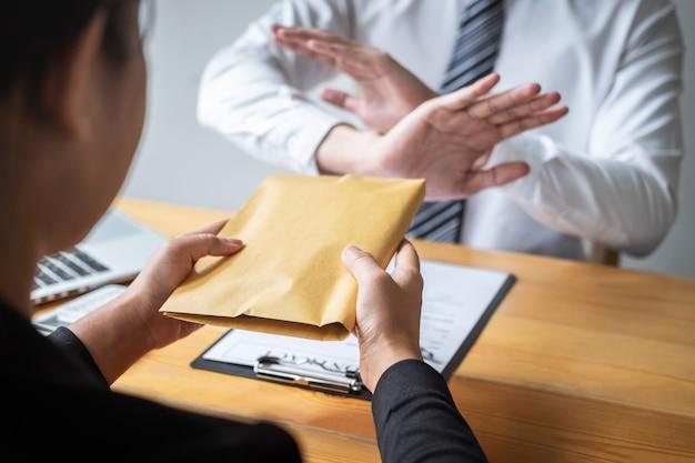 Uomo d'affari che rifiuta e non riceve banconote in denaro nell'offerta busta da parte delle donne