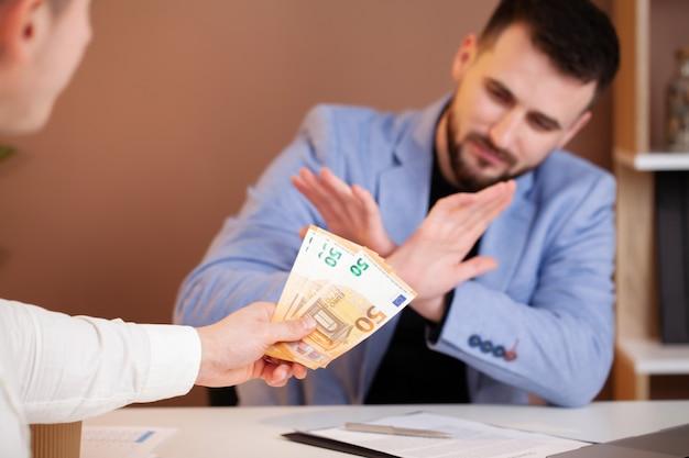 Uomo d'affari che rifiuta i soldi per prendere la bustarella il concetto di corruzione e anti corruzione
