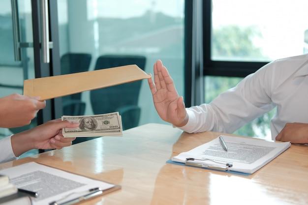 Uomo d'affari che rifiuta la banconota dei contanti dei soldi dalla donna. l'uomo onesto rifiuta di prendere la bustarella. corruzione, corruzione, venalità.