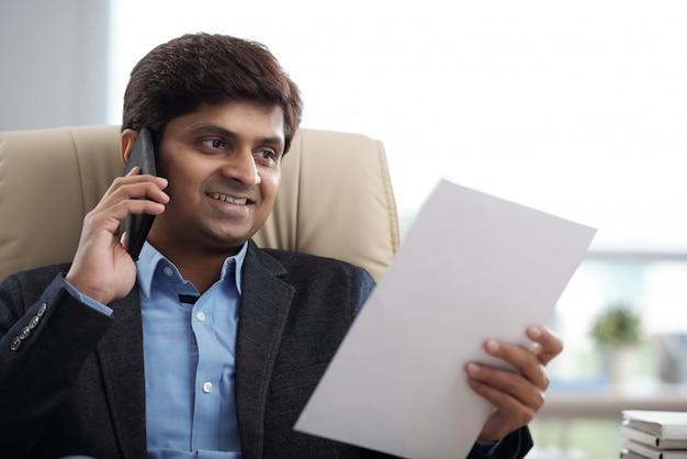Uomo d'affari che rivolge al telefono
