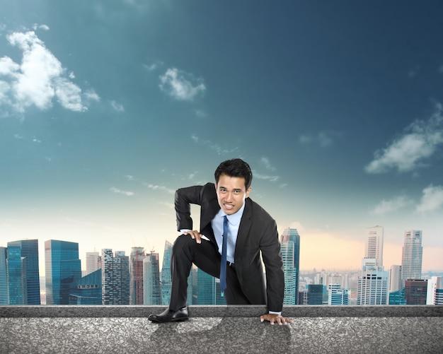 Uomo d'affari che scala alla cima dell'edificio