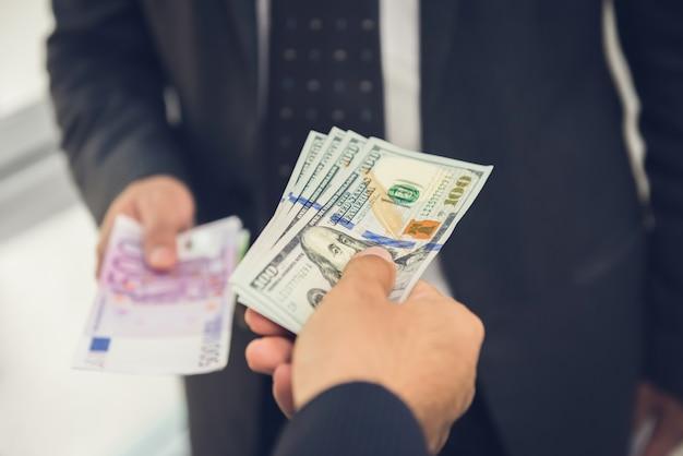 Uomo d'affari che scambia i dollari americani dei soldi con euro valuta