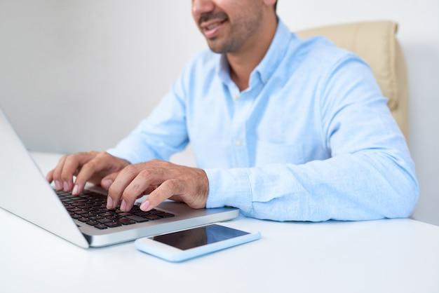 Uomo d'affari che scrive sul computer portatile