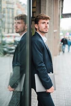 Uomo d'affari che si appoggia con confidenza su una parete di vetro scuro che tiene compressa digitale disponibile