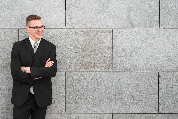 Uomo d'affari che si appoggia contro il muro