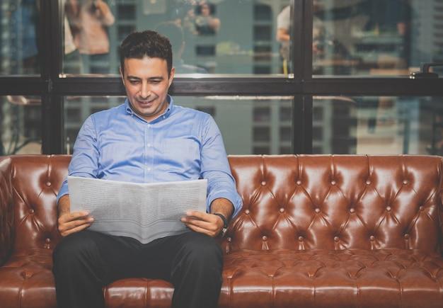 Uomo d'affari che si rilassa e che legge il giornale di notizie dal mondo degli affari sul sofà nell'ufficio