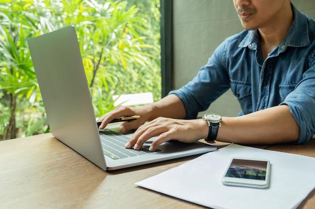 Uomo d'affari che si siede al caffè che lavora su klaptop con smartphone e lavoro di ufficio sul tavolo