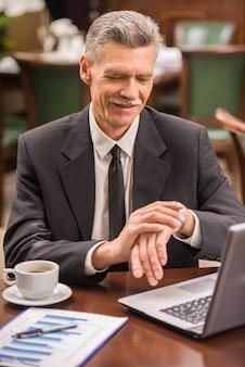 Uomo d'affari che si siede alla tavola in caffè e che esamina gli orologi.