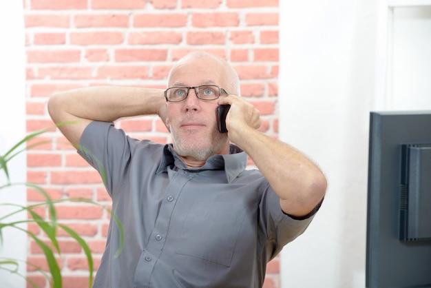 Uomo d'affari che si siede allo scrittorio che parla sul telefono