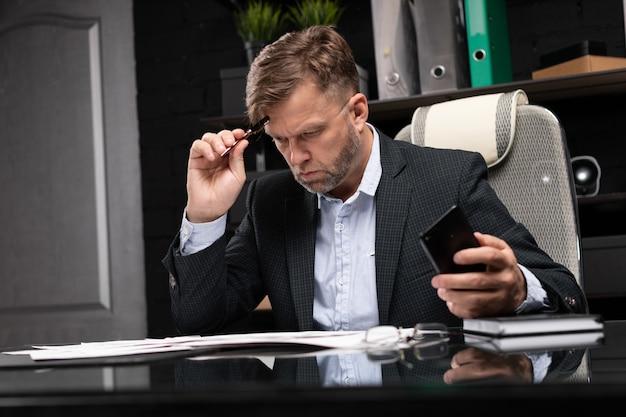 Uomo d'affari che si siede allo scrittorio del computer con un telefono in sue mani e che pensa ai documenti