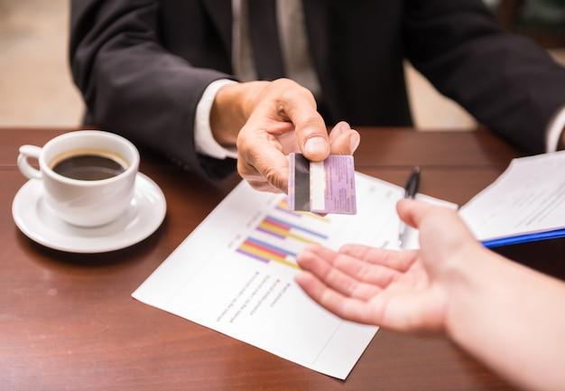 Uomo d'affari che si siede in caffè e che dà la carta di credito al cameriere