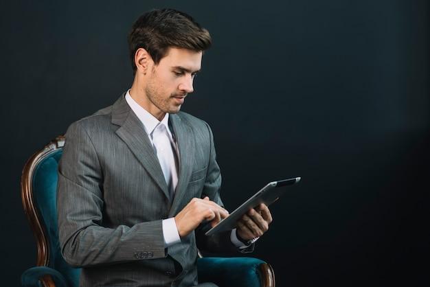 Uomo d'affari che si siede sulla poltrona in vestito facendo uso della compressa digitale contro fondo nero