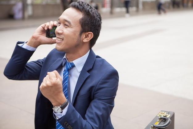 Uomo d'affari che si siede sulla scala durante callling il telefono, con la priorità bassa dell'edificio per uffici