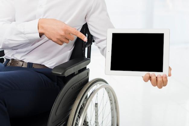 Uomo d'affari che si siede sulla sedia a rotelle che indica il suo dito alla compressa digitale