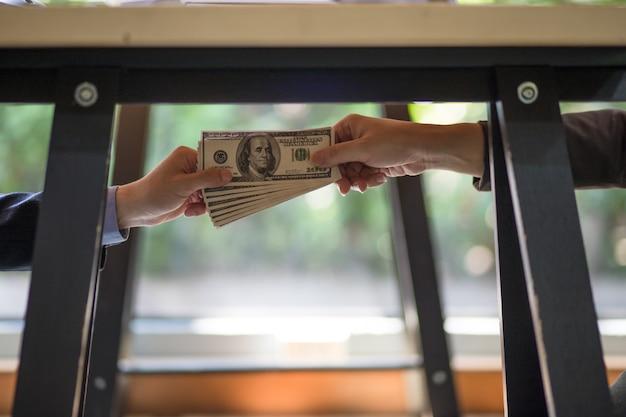 Uomo d'affari che sigilla l'accordo con una stretta di mano e riceve una tangente.