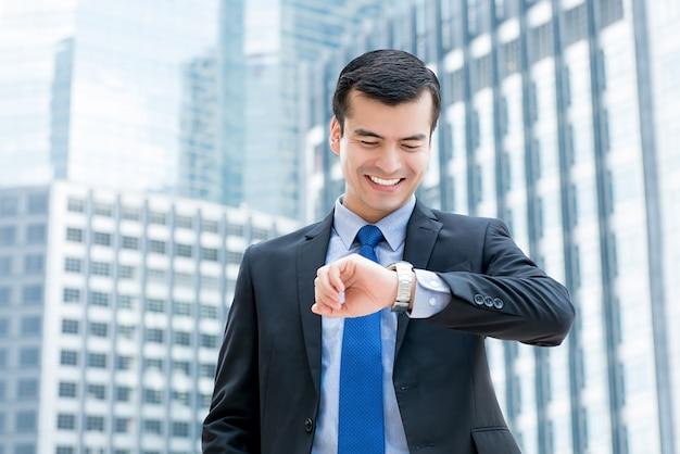 Uomo d'affari che sorride e che esamina il suo orologio con un momento felice nella città