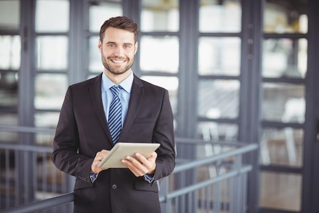 Uomo d'affari che sorride mentre per mezzo della compressa digitale