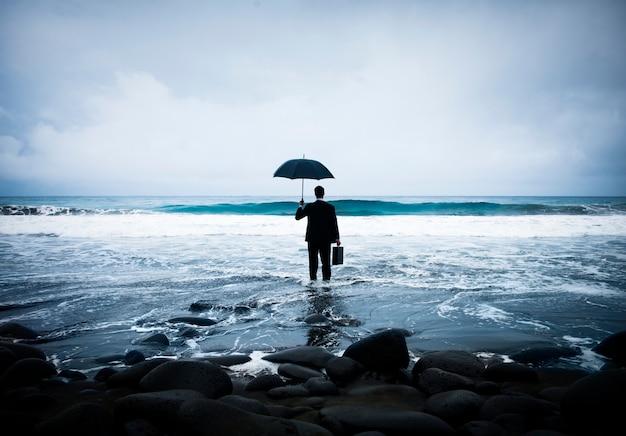Uomo d'affari che sta con un ombrello nell'oceano