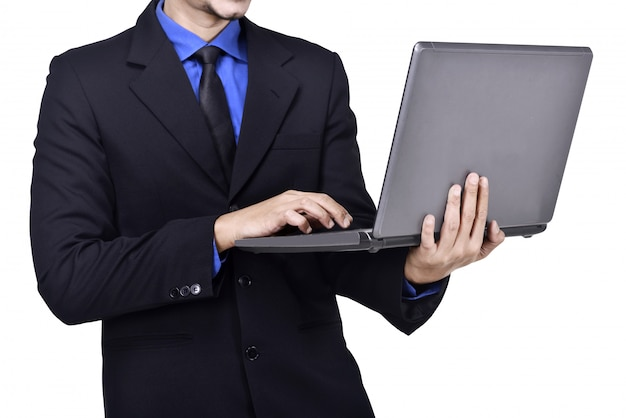 Uomo d'affari che sta mentre scrivendo sul computer portatile