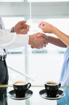 Uomo d'affari che stringe le mani e che dà biglietto da visita al collega