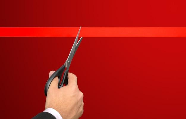 Uomo d'affari che taglia nastro rosso con le paia di forbici