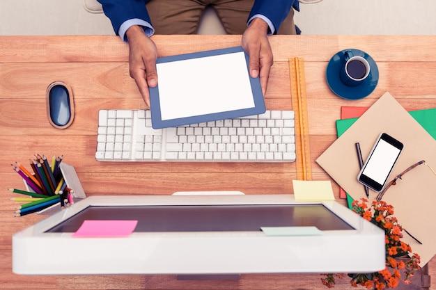 Uomo d'affari che tiene compressa digitale mentre sedendosi allo scrittorio del computer in ufficio creativo