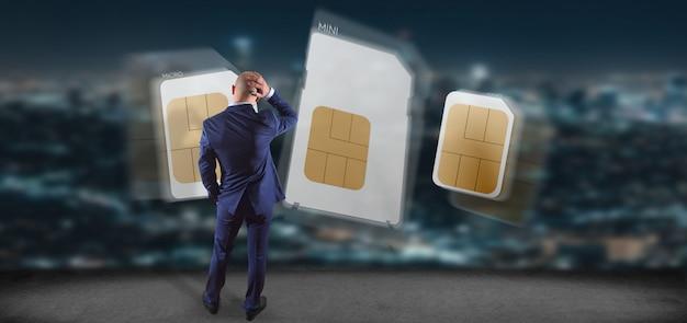 Uomo d'affari che tiene dimensione differente di una rappresentazione della carta 3d del sim dello smartphone
