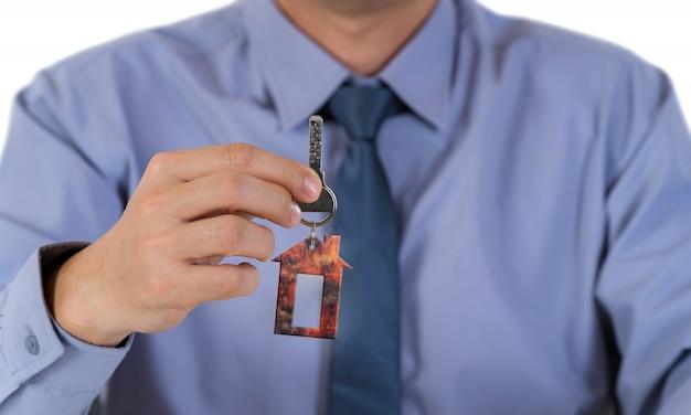 Uomo d'affari che tiene e che mostra una chiave della casa