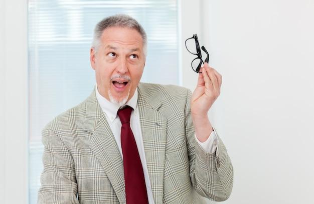 Uomo d'affari che tiene glassesand che ha un'idea