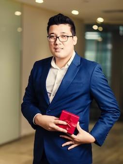Uomo d'affari che tiene il contenitore di regalo rosso
