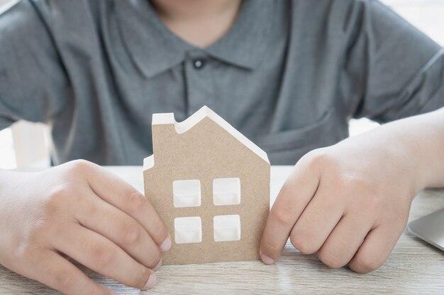 Uomo d'affari che tiene il mini modello della casa di legno sullo scrittorio, gestione della proprietà di idee
