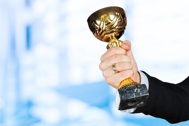 Uomo d'affari che tiene il trofeo della coppa d'oro