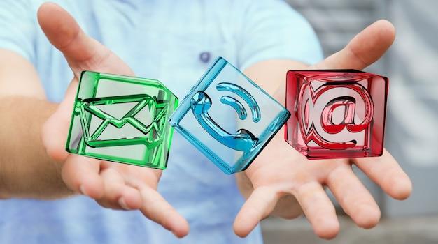 Uomo d'affari che tiene l'icona trasparente del contatto del cubo nella sua rappresentazione della mano 3d