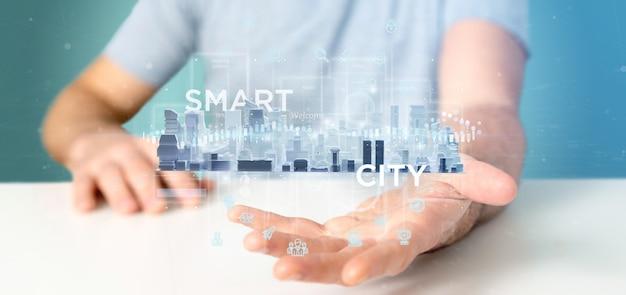 Uomo d'affari che tiene l'interfaccia utente della città astuta con l'icona, le statistiche e la rappresentazione di dati 3d