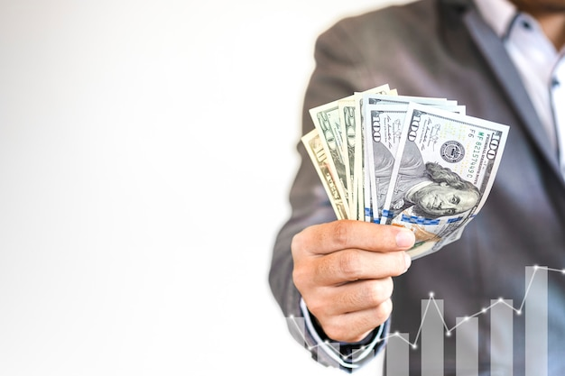 Uomo d'affari che tiene la banconota del dollaro americano con il grafico di crescita digitale di tecnologia
