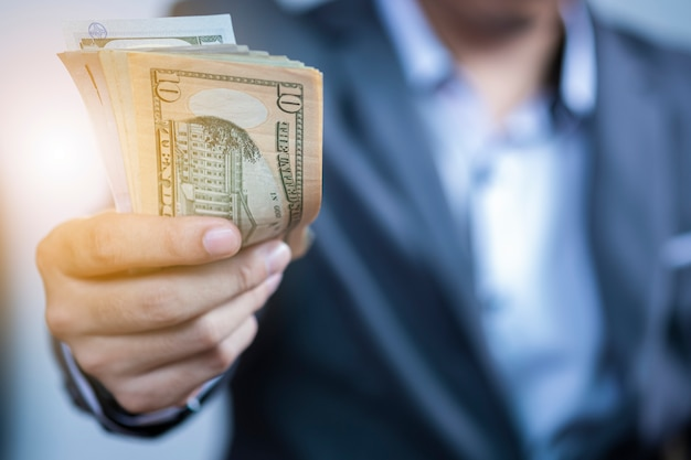 Uomo d'affari che tiene la banconota usd per il pagamento.