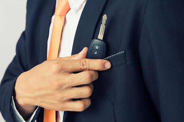 Uomo d'affari che tiene la chiave dell'automobile, fondo isolato