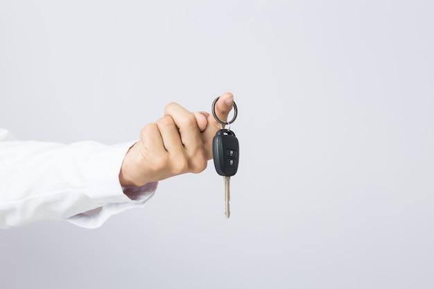 Uomo d'affari che tiene la chiave dell'automobile, isolata