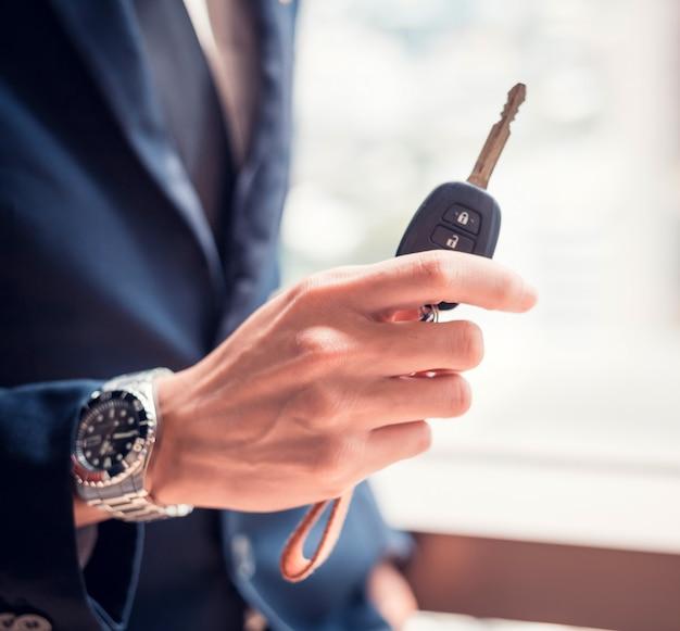 Uomo d'affari che tiene la chiave dell'automobile