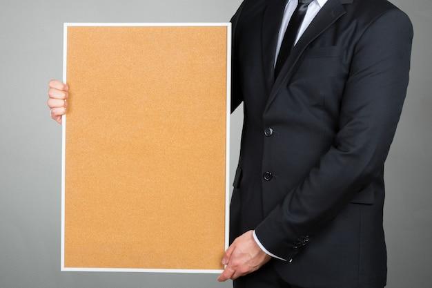 Uomo d'affari che tiene la cornice in bianco