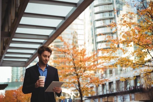 Uomo d'affari che tiene la tazza di caffè eliminabile e che per mezzo della compressa digitale