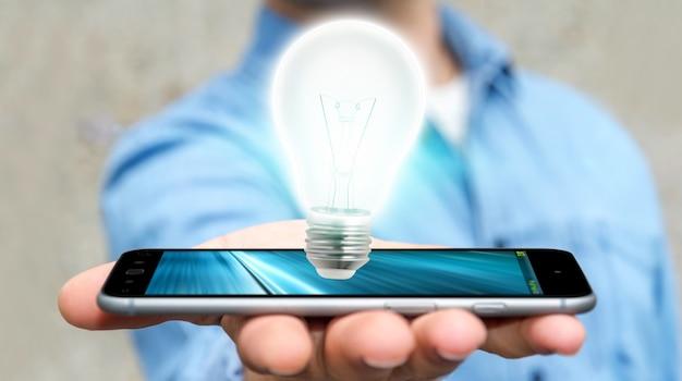 Uomo d'affari che tiene lampadina brillante sul telefono cellulare