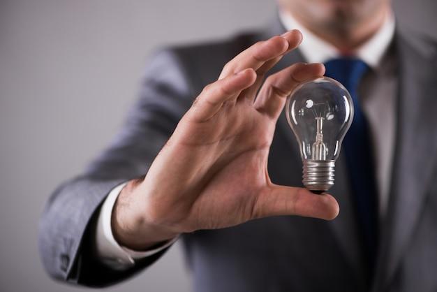 Uomo d'affari che tiene lampadina nel concetto di creatività