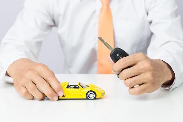 Uomo d'affari che tiene le chiavi di un'auto e un modello di auto in miniatura, affari auto e concetto finanziario
